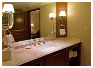 A bathroom with granite sink and counter surface
